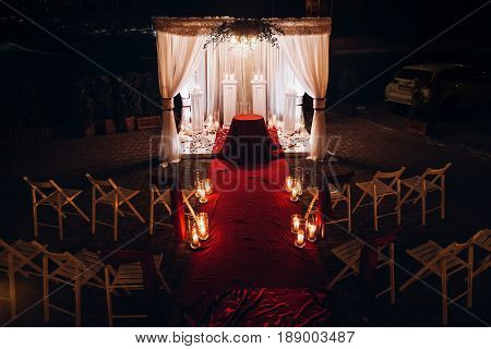 Wedding Venue Aisle With Candles In Glass Lanterns And Arch, Stylish Wedding Decor For Evening Weddi