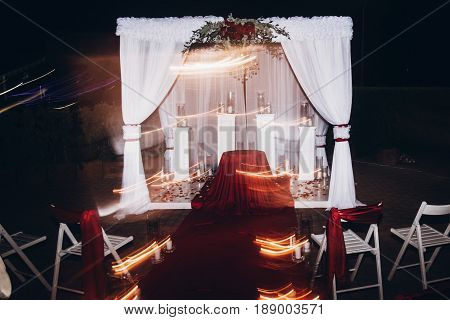 Wedding Evening Decor For Ceremony, Venue Aisle With Candles In Glass Lanterns And Arch, Stylish Wed