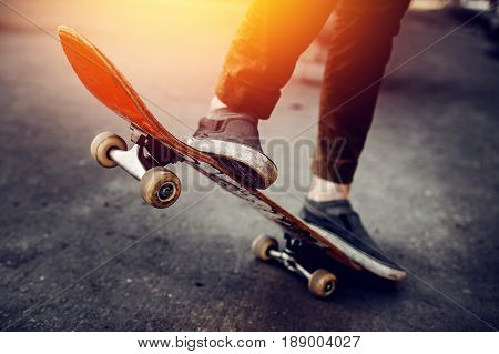 Close-up of a male guy on a skateboard doing trick kicks in shoes. The concept of doing street sports skateboarding. Sunset, toning pictures.