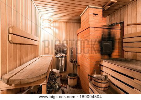 Empty wooden sauna room with ladle, bucket ready to be used.