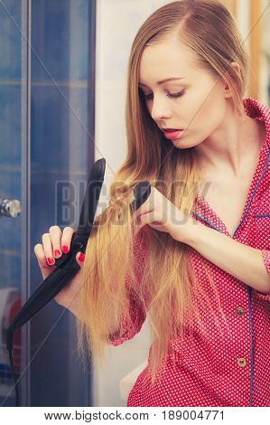 Woman Straightening Her Long Blond Hair