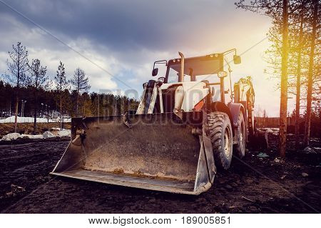 Machine tractor loader on a sky background with a glare from the sun. Concept road construction.