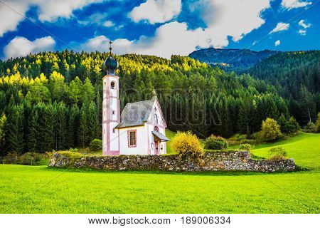 The church of St. Mary Magdalene and bell tower in a mountain valley. Dolomites, Tyrol, summer sunset. The concept of eco-tourism