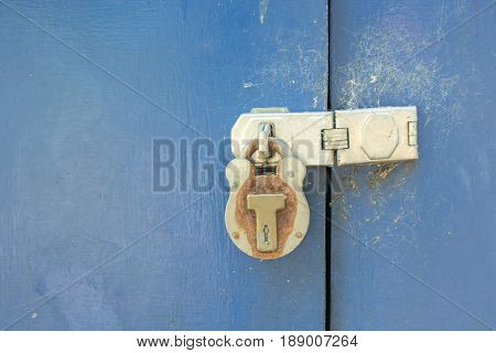 Closeup of blue painted barn door with old rusted pad lock and hasp