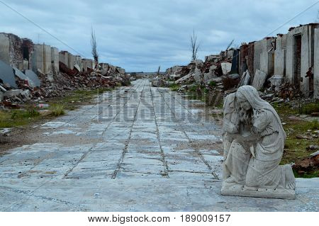 Religious statue witnessing the destruction of nature in a cemetery in the province of Buenos Aires