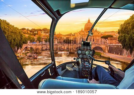 Rome at Sunset with San Pietro basilica, Sant'Angelo bridge and Tevere river in Roma, Italy Helicopter cockpit with pilot arm and control console inside the cabin.
