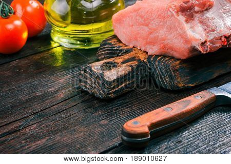 Uncooked pork meat loin on rustic wooden cutting board with fresh tomatoes and olive oil in cruet on old dark wood table. Close-up angle view