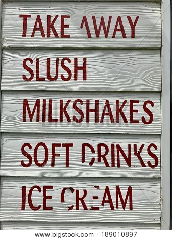Takeaway sign slush milkshakes soft drinks ice cream red font white paint wooden background