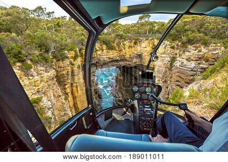 Helicopter cockpit with pilot arm and control console inside the cabin on Tasman Arch in the Tasman National Park, Tasman Peninsula south east coast of Tasmania, Australia.