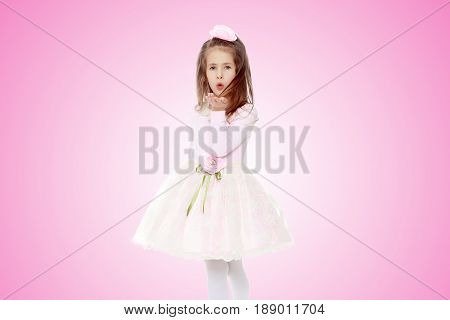 Dressy little girl long blonde hair, beautiful pink dress and a rose in her hair.She sends a kiss.Pale pink gradient background.