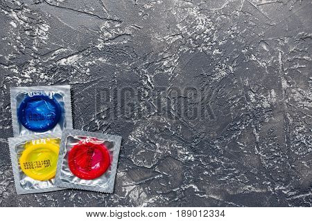 safe sex with condom contraception on dark desk background top view mock up