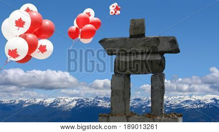 Canada day maple leaf balloons floating over an inukshuk in the Rocky mountains.