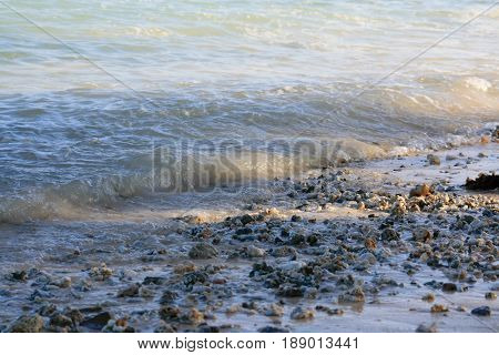 Waves on a rocky shore Small waves gently slapping against a rocky shoreline