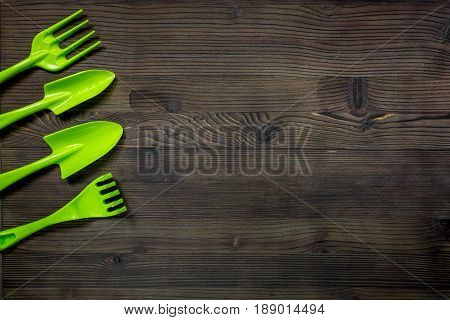 green garden tools for planting flowers at home on wooden table background top view space for text