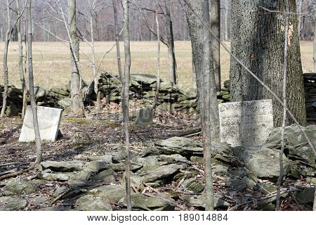 Old grave markers in a graveyard surrounded by stonewalls.