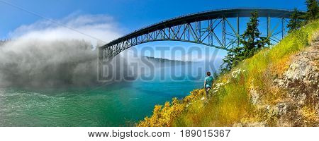 Woman meditating on seashore by the bridge. Deception Pass Bridge. Anacortes. Whidbey Island. Strait of Juan de Fuca. Puget Sound. WA. USA.