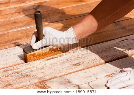 Painter staining deck boards with transparent protective outdoor decking paint applying stain with brush with special attention to the gaps