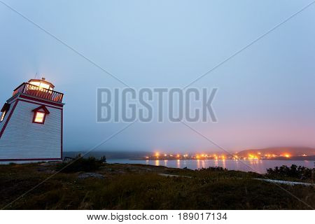 Foggy twilight at lighthouse on Fort Point with village of Trinity in the distance Newfoundland NL Canada