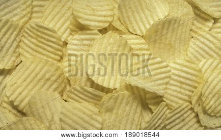 Close up crispy potato chips top view backgrounde. Ruffles form.