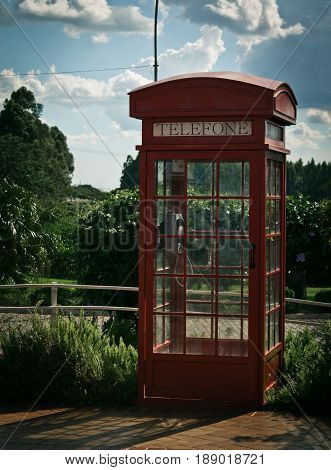 View of old red sunlit telephone booth against sky