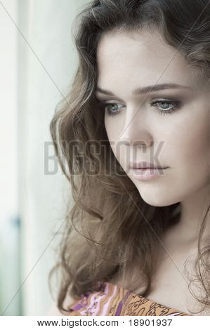 attractive young adult looking at the window with serious look
