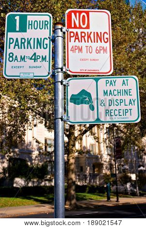 Three parking signs on one pole in Sacramento, California