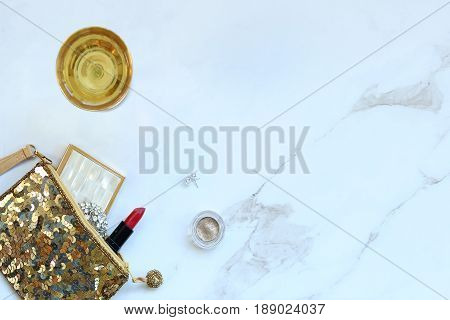 Gold sequined bag with fashion and beauty supplies spilling out. Champagne glass. White marble copy space.