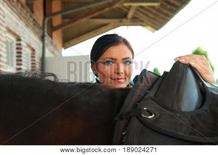 young woman saddling her horse on horse ranch