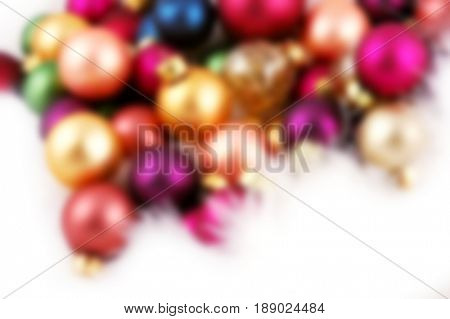 Pile of Christmas ornaments nestled in a bed of white feathers - blurred image, background