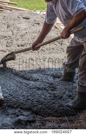 Construction worker spreading poured concrete with a shovel