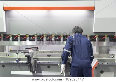 The technician operator use hydraulic bending machine. Metal working manufacturing concept
