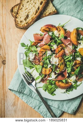 Arugula, prosciutto, mozzarella and grilled peach salad in white plate over blue napkin and wooden board, top view, vertical composition