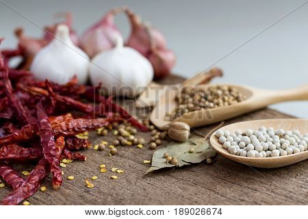 Food ingredients peppercorn and red dry chilli peppers on wooden table asian food cooking concept.