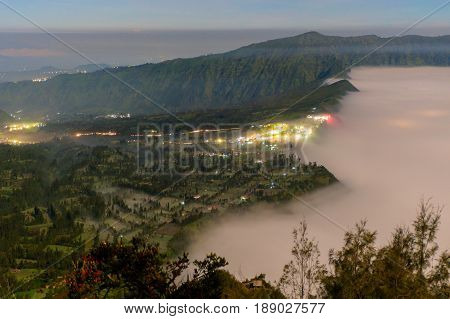 Beautiful foggy landscape of Cemara Lawang village near Mount Bromo during a pre-dawn sky above the clouds over Bromo Tengger Semeru National Park East Java Indonesia.