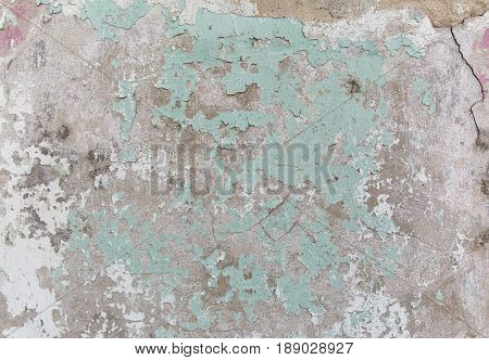 Old painted wall. Green and damage surface. Peeling paint background. Stone demaged backdrop