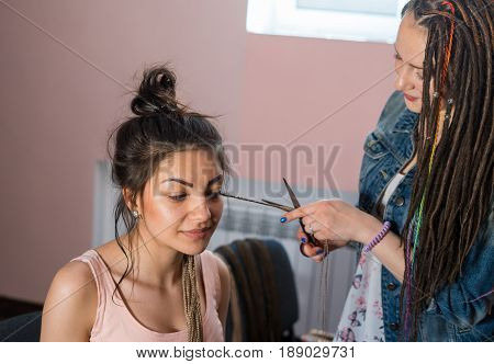A hair stylist cuts Zizi cornrows from young and beautiful girl. new hairstyle without dreadlocks plait