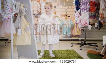 A nice little girl trying on a smart dress in front of a mirror in a children's clothing store