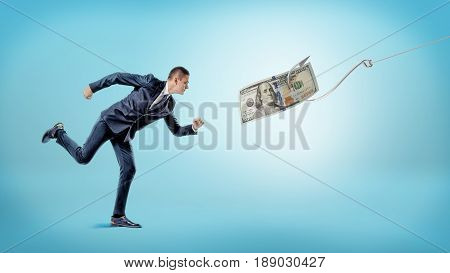 A businessman running after a dollar bill that's attached to a silver hook. Carrot and stick. Financial motivation. Earnings and income.