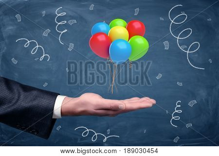 A businessman's hand turned up with a set of colorful balloons tied together hovering above it on chalkboard background. Business celebration. Employee of the month. Job bonuses.