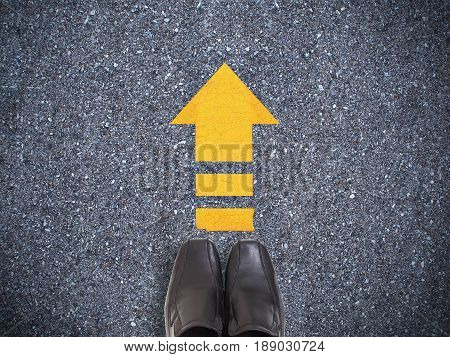 Selfie black shoes on concrete road with yellow arrow line. Go ahead concept.
