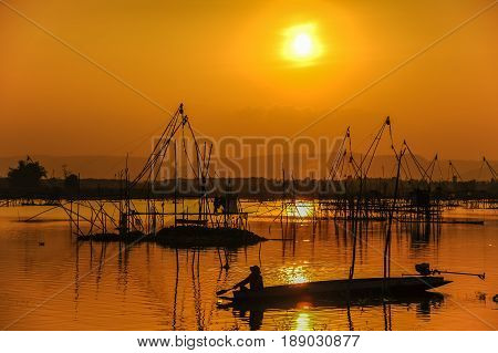 Traditional fishing tool and fishing boat in swamp during sunset
