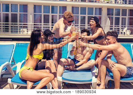 Cheers. Group of cheerful friends drinking cocktails and beer during party at the pool. They clink glasses. Happy friends