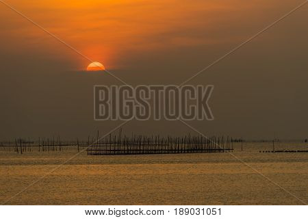 Sunset over the sea with fisherman's tool