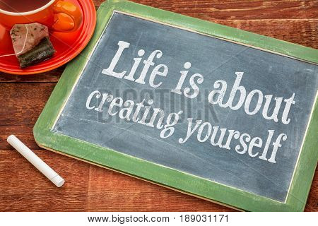 Life is about creating yourself  - motivational text on a slate blackboard with chalk and cup of tea