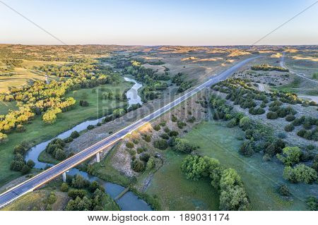 aerial view of a highway and bridge over the Dismal River in Nebraska Sand Hills near Thedford, spring scenery lit by sunrise light