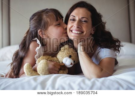 Daughter kissing her mother on cheek in bedroom at home