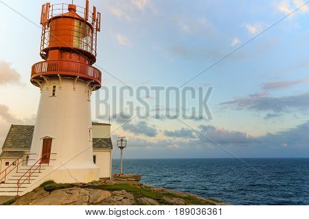 Historic red white lighthouse on the edge of rocky sea coast South Norway Lindesnes Fyr beacon
