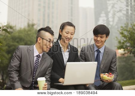 Chinese business people using laptop outdoors