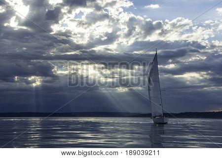Magic rays penetrate clouds at sunset behind sailboat.