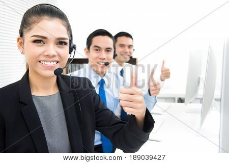 Call center (or telemarketer) team giving thumbs up